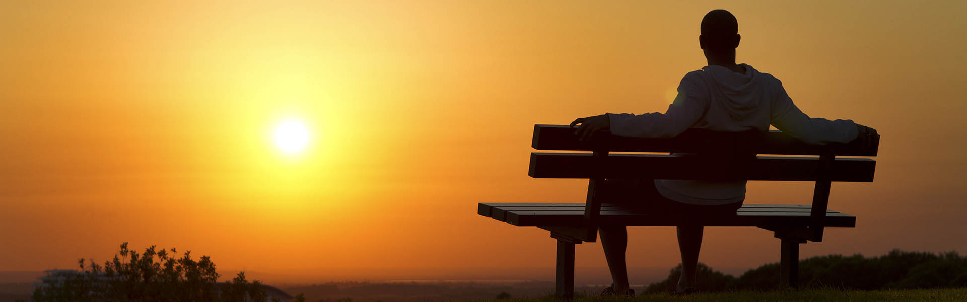 man on bench watching a sunset enjoying life